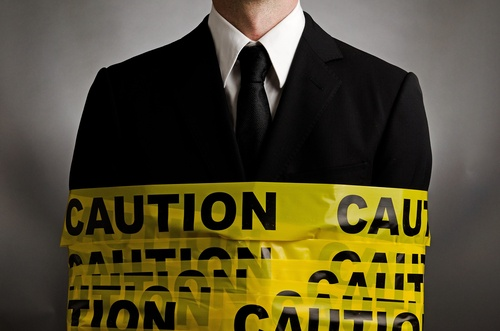 Business man in suit and tie wrapped with yellow caution tape
