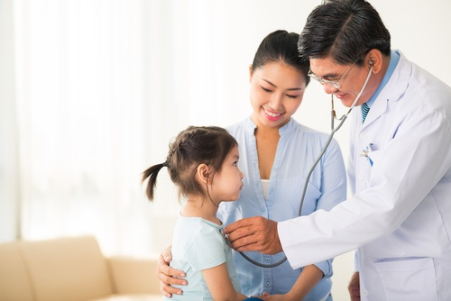 Male pediatrician using stethoscope on young girl with mother nearby